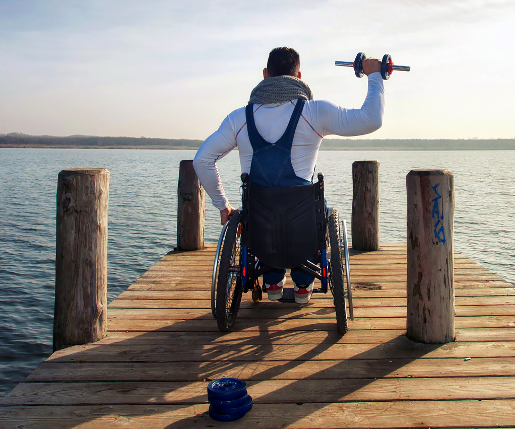 young man in wheelchair outside in nature, dumbbell training for fitness