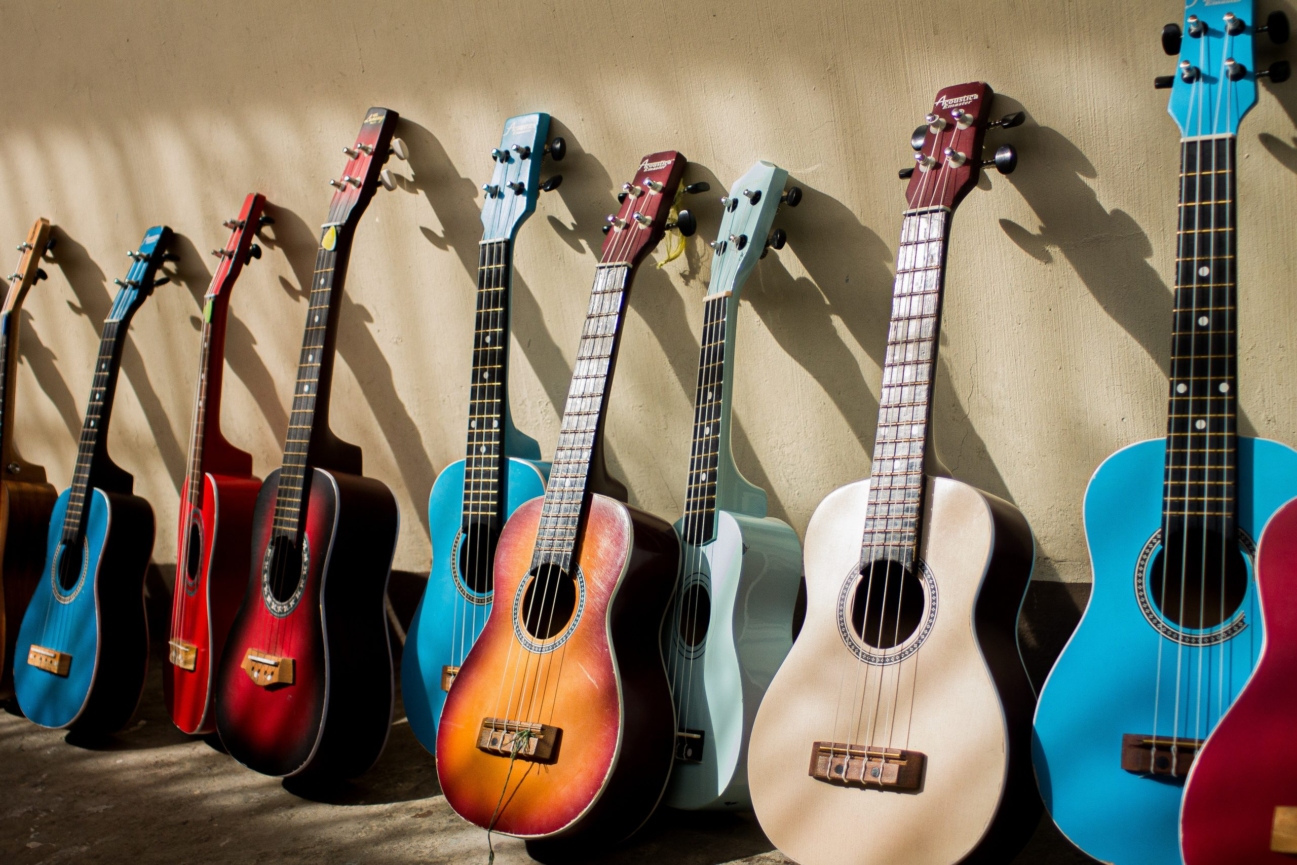 different guitars leaning against the wall