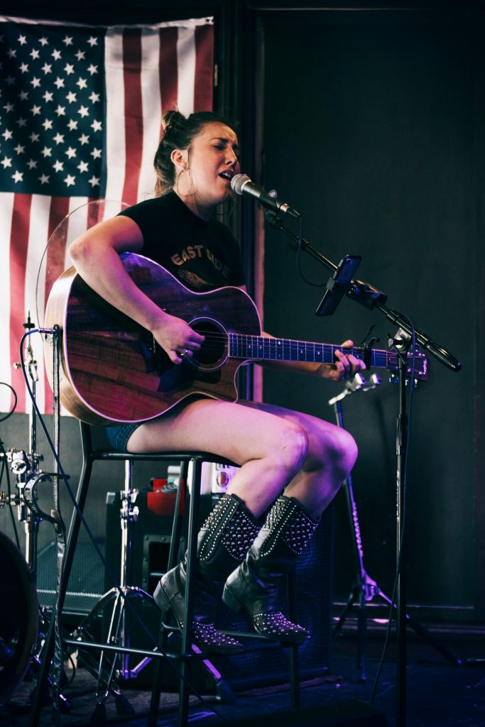 girl singing and playing guitar live on stage